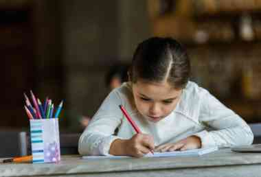 ittle child sitting at table and drawing in scrapbook at home