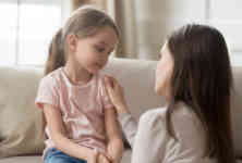 Loving mom talking to upset little child girl giving support