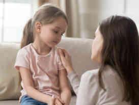 Loving mom talking to upset little child girl giving support